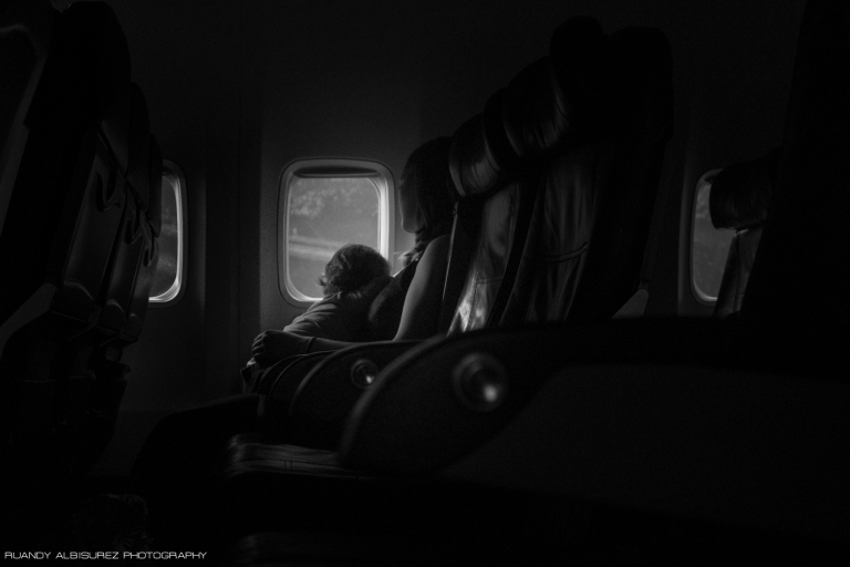 Portrait of a mother with her daughter sleeping on her lap during most of the flight. The image of them was too amazing to not snap a shot of.